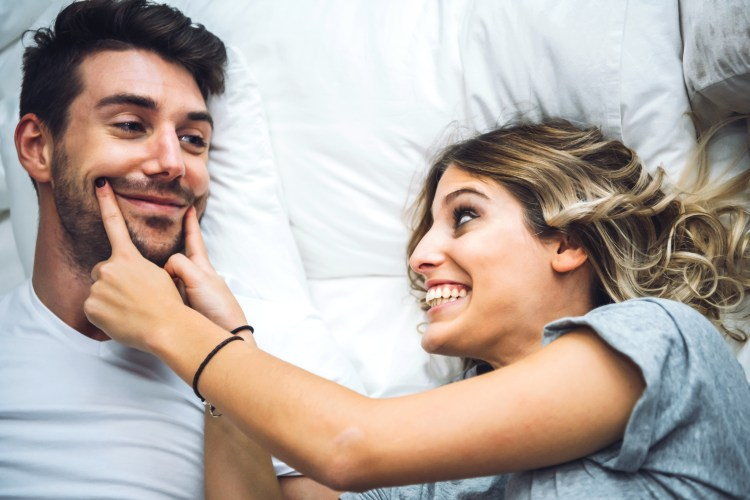 Cheerful couple playing in bed