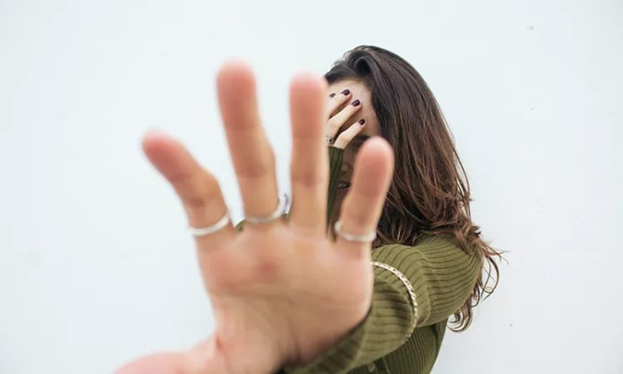 A woman with her face covered by a hand