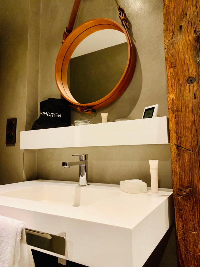 salle de bain de la suite Cuir, miroir rond et vasque moderne