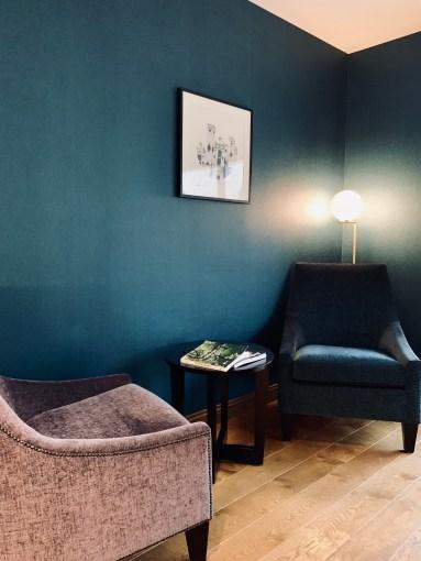 fauteuils longe côté bar devant mur bleu canard
