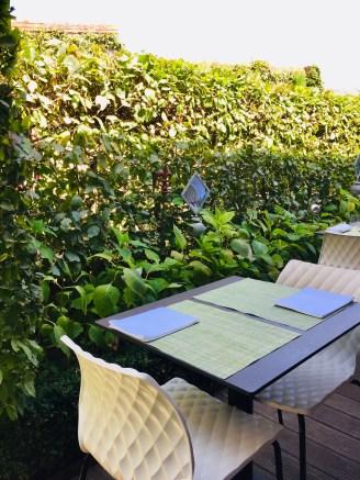 Table mise sur la terrasse haie verdoyante