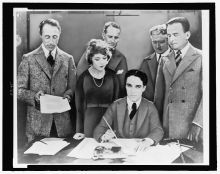 d.w. griffith, mary pickford, charlie chaplin (seated) and douglas fairbanks at the signing of the contract establishing united artists motion picture studio