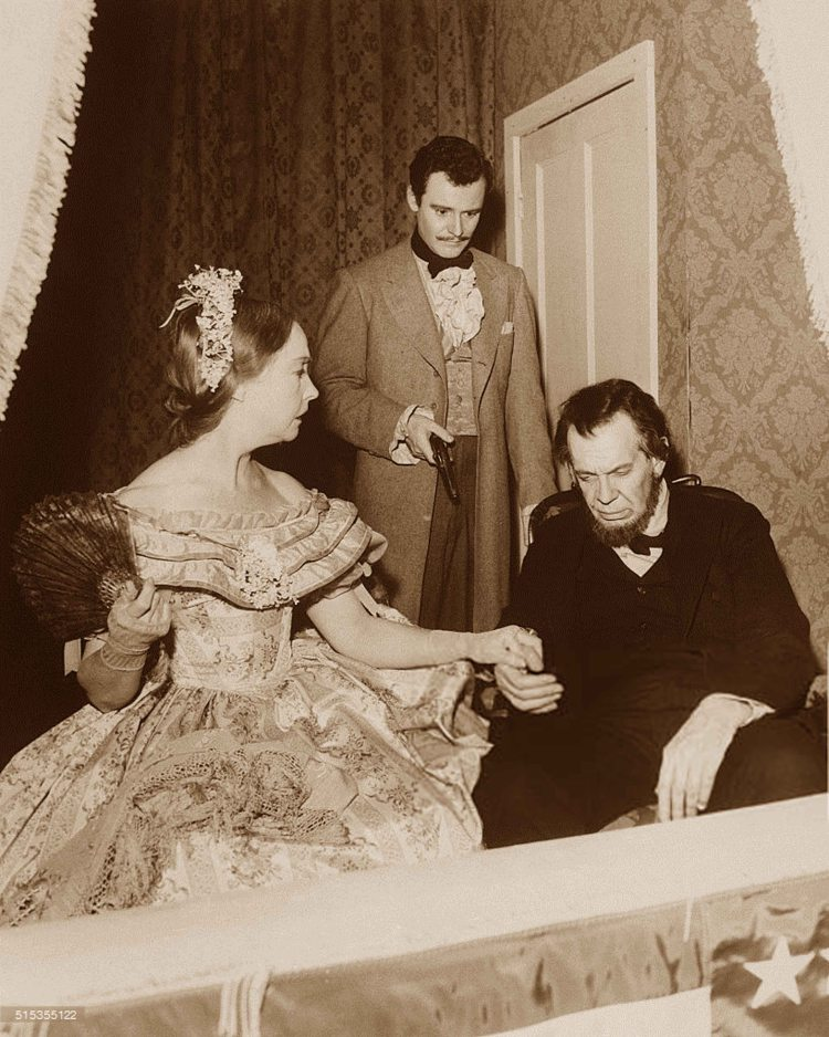 as Mary Todd Lincoln, holds hands with Canadian actor Raymond Massey (1896 - 1983), as President Abraham Lincoln, as they watch a play from the balcony while American actor Jack Lemmon