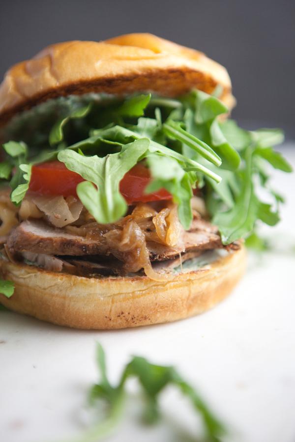 Pork Tenderloin Sandwich with lots of arugula on a cutting board
