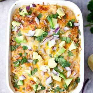 Spaghetti squash enchilada bake topped with avocado, cilantro, and onions