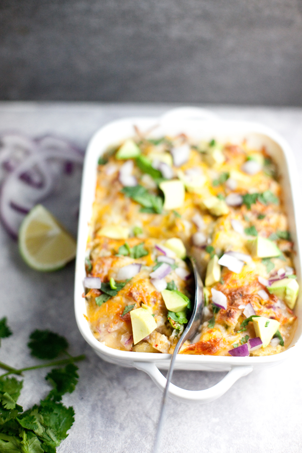Spaghetti squash enchilada bake topped with avocado, cilantro, and onions