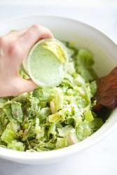 Pouring creamy jalapaño avocado dressing on a Mexican caesar salad