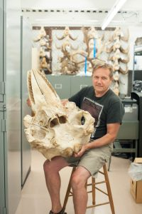 Biologist at the RBC Museum holding Orca Skull