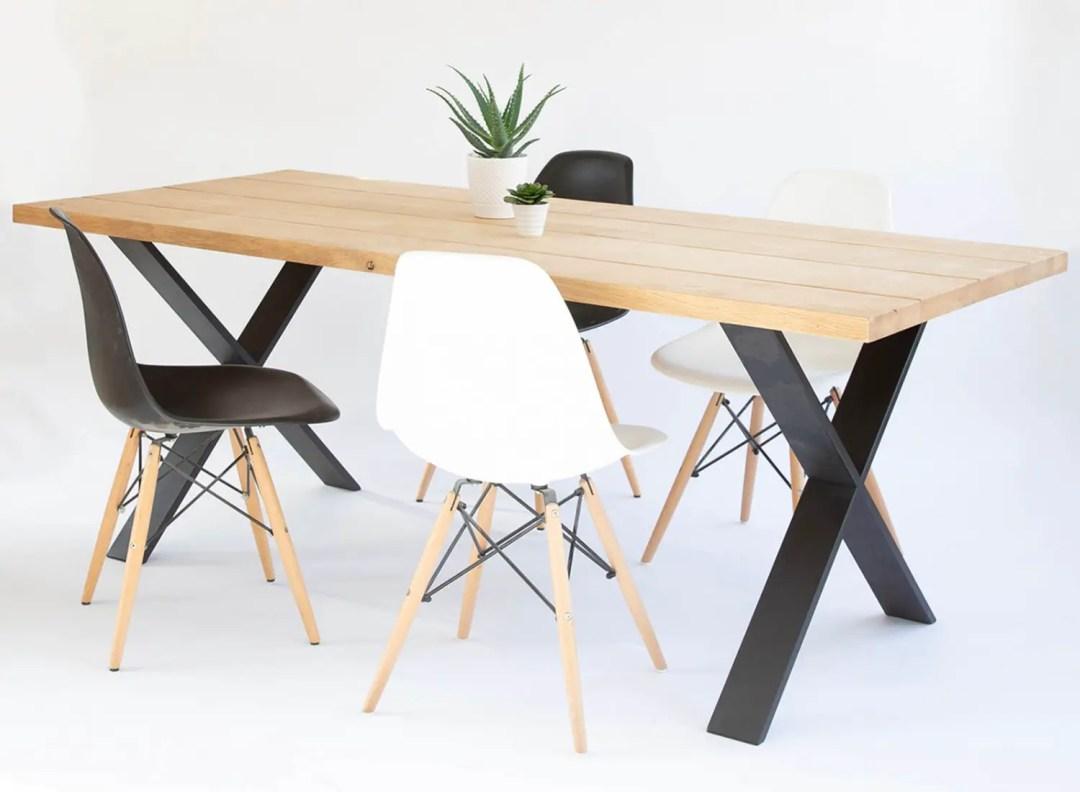 Table effet planches en bois massif avec un piétement en X.