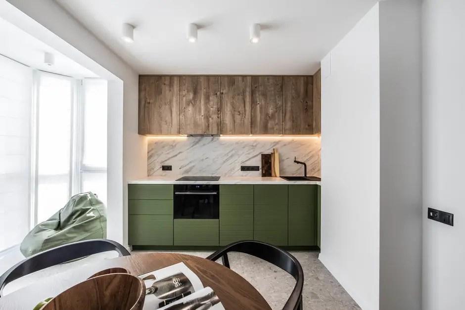Cette cuisine scandinave utilise les placards en bois en haut pour ajouter du chaleur et ses placards verts en bas ajoute du couleur.