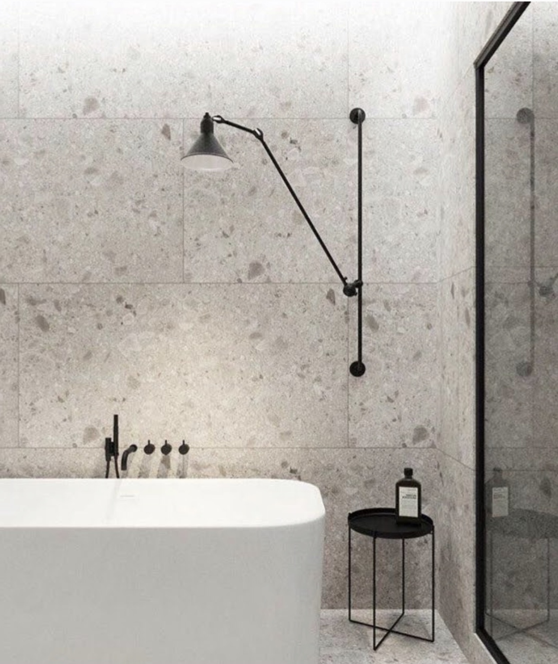 Une salle de bain aménagée des grands carreaux en pierre de couleur neutre.