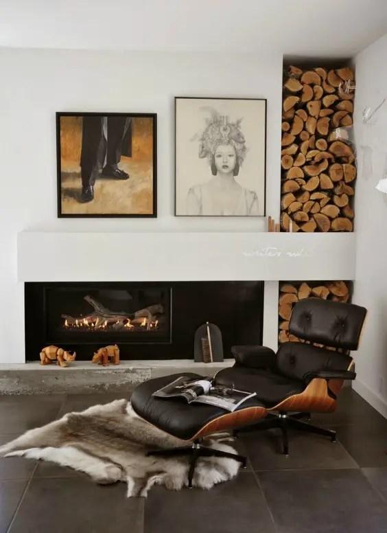 Un fauteuil bas en cuir noir du style moderne à côté d'un coin du feu.