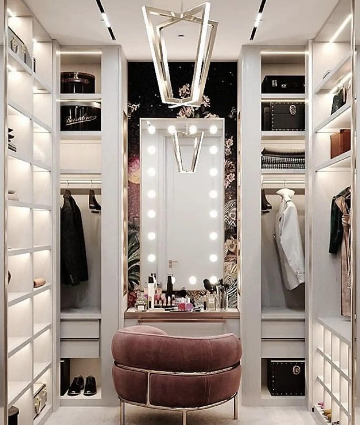 La vanité est exposé. Il possède un miroir avec les ampoules rondes et un fauteuil rose.
