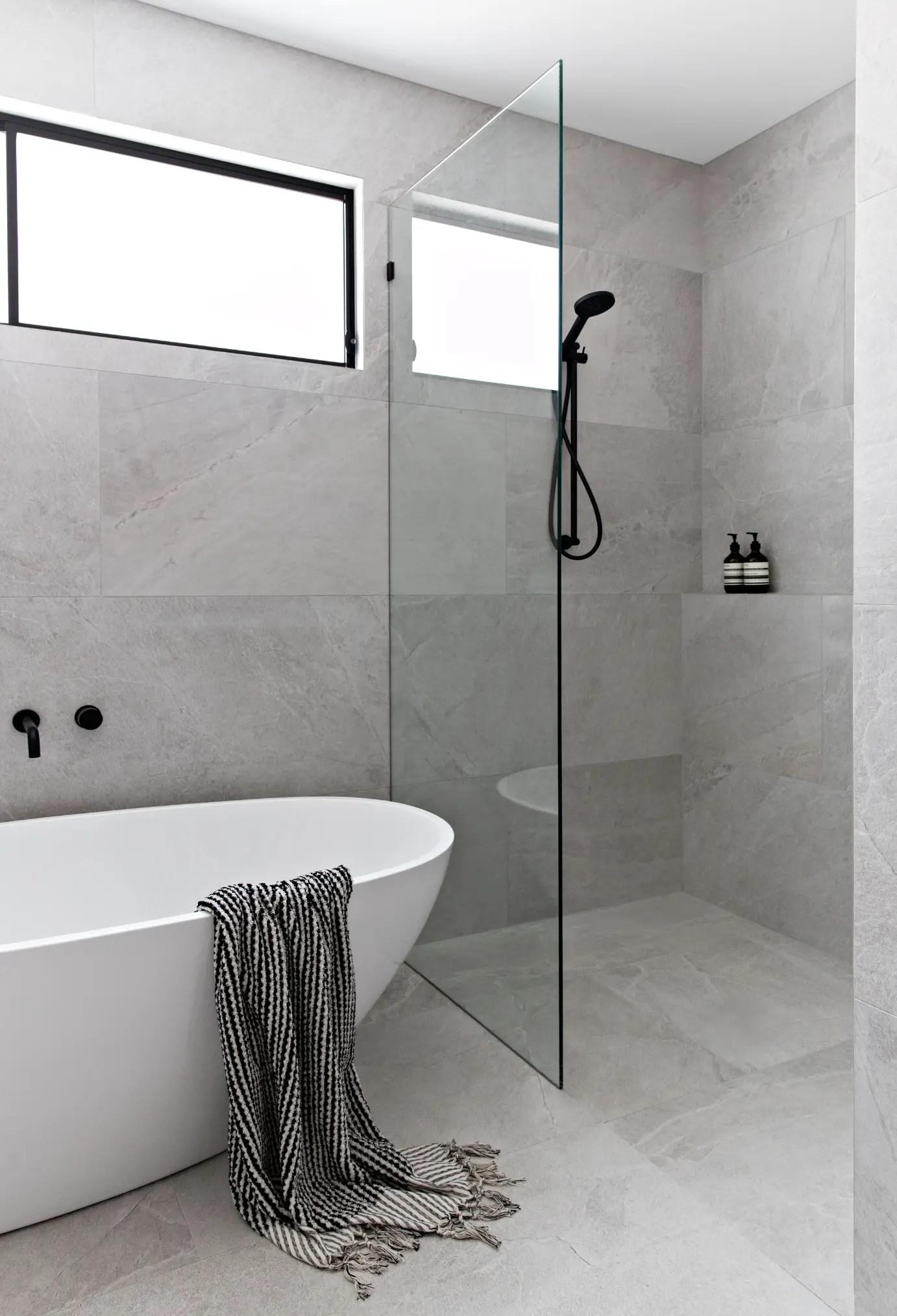 Avec cette tendance déco 2020 cette salle de bain semble plus grande avec les grands carreaux en pierre gris.