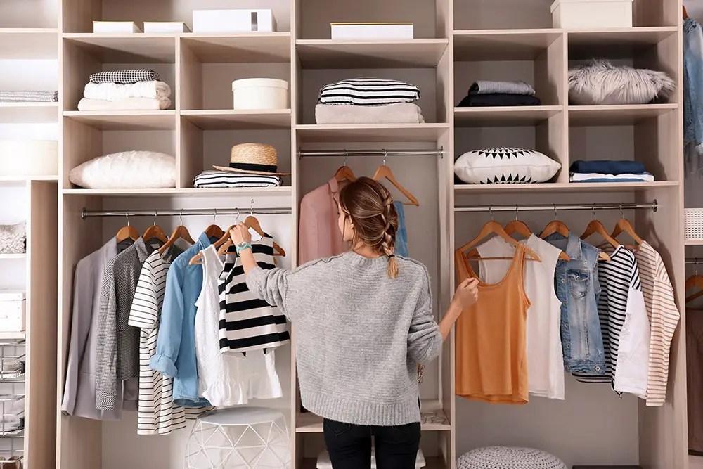 jeune femme qui choisit ses vêtements dans un dressing