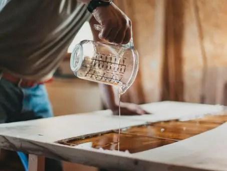 artisan qui verse de la résine d'epoxy dans la moulure d'une table en bois