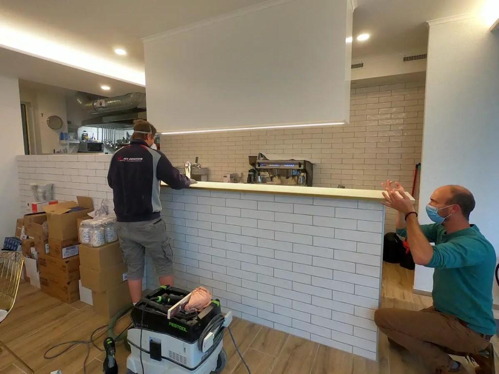 agencement d'un restaurant : artisans en train de poser un comptoir de bar