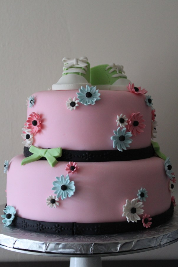 pink cake with green baby sneakers