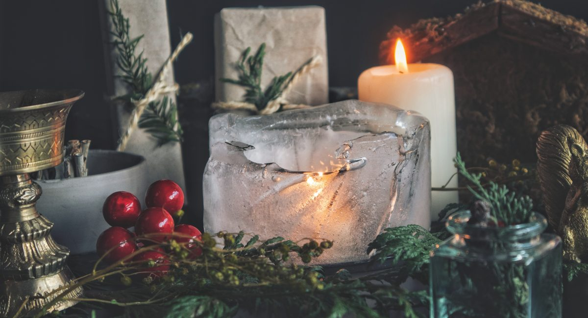 Close up of candle burning in ice. Festive Yule winter solstice (Christmas) set up on wiccan witch altar, filled with nature items, like evergreens, gifts presents, white candle, gold incense burner