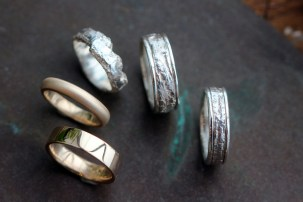 From left: gold square edge band in a high polish, half round gold band in matte finish, three mens bands cast from real tree bark