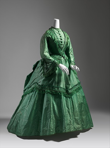This day dress, is British from c. 1870 and you can see the bustle profile consisting of several layers of draped fabric arranged to draw the eye towards the rear.