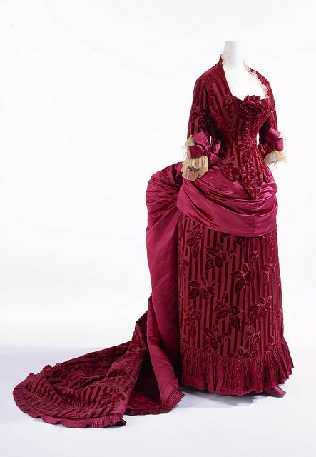 Dinner Dress, French, c. 1883, Worth. Wine-red silk satin cut velvet with stripes and leaf pattern; figured additional cut velvet layer on leaf pattern; set of bodice and skirt with bustle; tulle and silk satin bows at cuffs; apron-shaped overskirt draped toward back. This dress of silk satin and cut velvet stripes is scattered with a roseleaf motif of cut and uncut velvet, causing shading of the motif. These beautiful materials, with a woven thickness created using complex techniques, show the high quality of Lyon silk textile. The overskirt, draped and gathered into an apron style, and the train greatly contribute to the dignified production of this bustle style dress. Kyoto Costume Institute (AC9712 98-29-2AB)