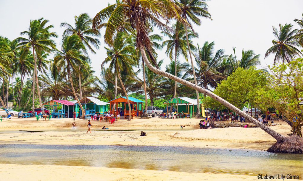 Colorful fish shacks, river and sand at Playa Arroyo Salado, Dominican Republic.