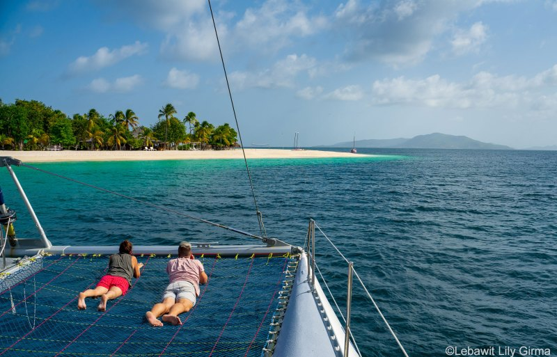 Two people on catamaran sailing towards offshore Palm Island Grenadines