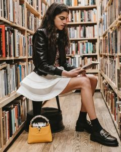 Leandra Medine Cohen sitting surrounded by books in a library