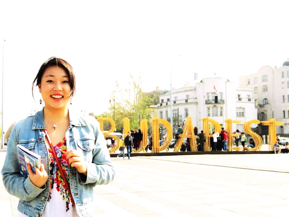 Smiling Girl holding a guidebook.