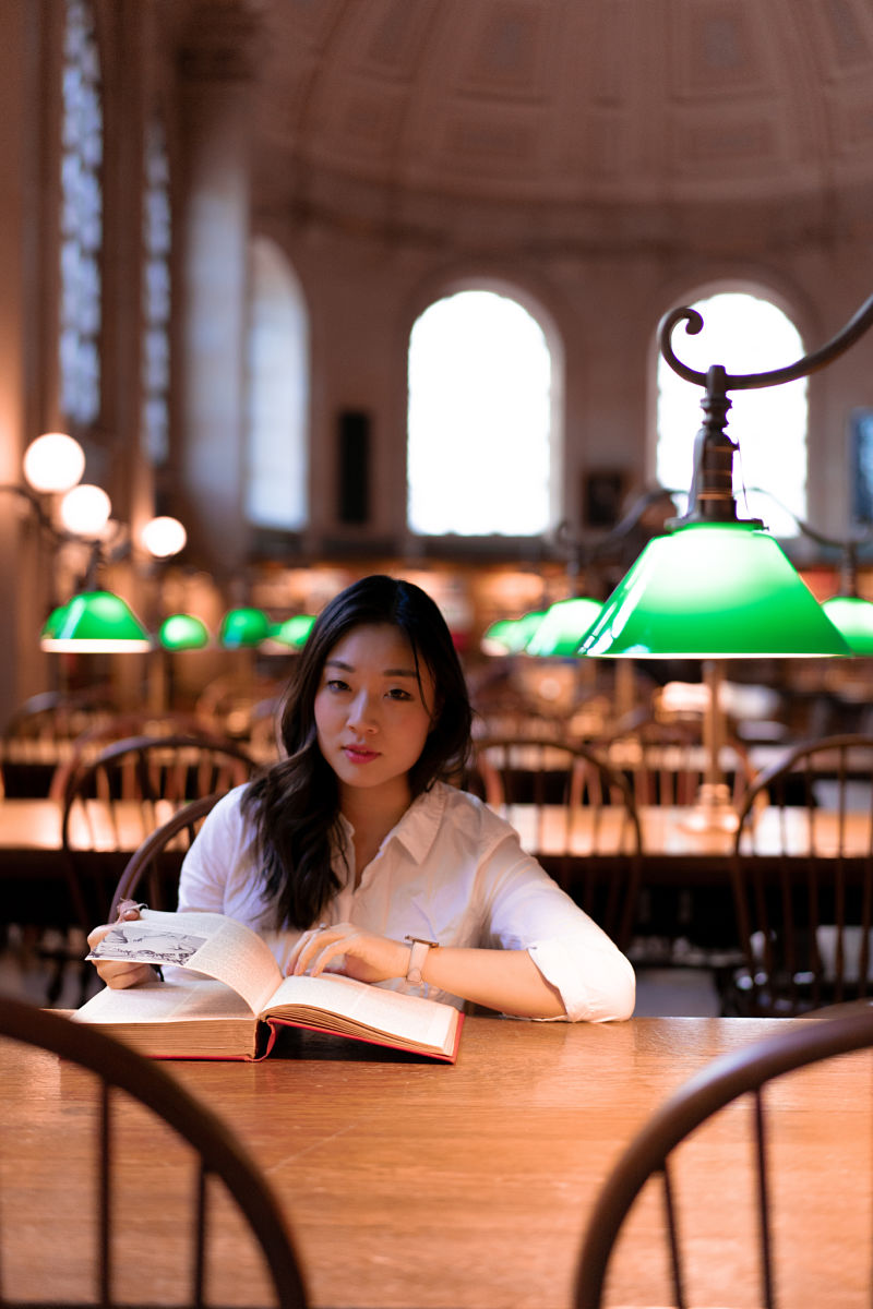 A portrait photo of a young woman of East Asia descent in the Bates Reading Room at Boston Pubic Library as one of the top things to do in Boston