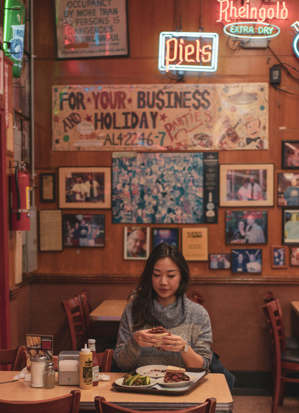 A girl eating a pastrami sandwich in Katzs deli in new york city