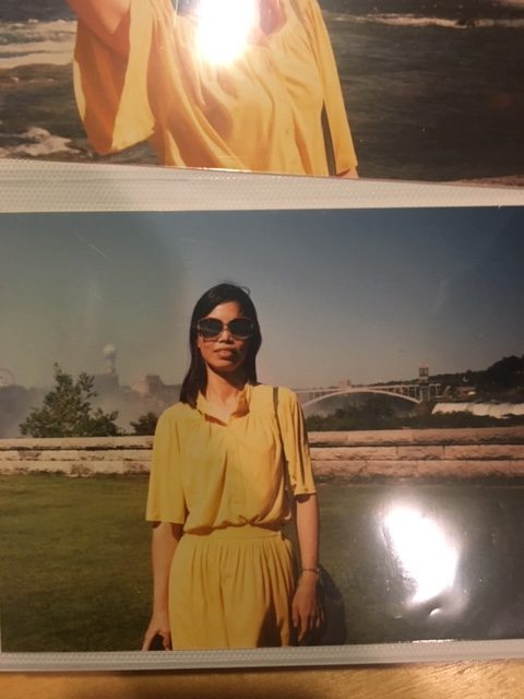 A woman of East Asian descent wearing dark sunglasses and in a yellow dress