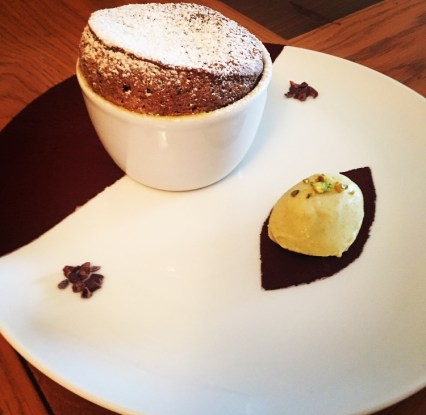 Decadent Chocolate Soufflé in a ramekin with pistachio ice cream. Served on a white plate.