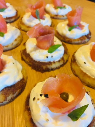 Easy blini's with smoked salmon and crème fraiche served on a wooden tray