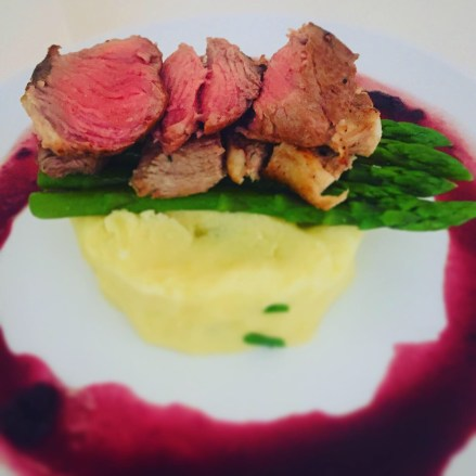 Lamb, asparagus with chive mashed potatoes on a white plate with a red wine sauce.