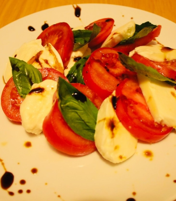 Caprese Salad with mozzarella, plump tomatoes and sweet basil. Drizzled with balsamic reduction