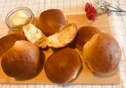 Soft Fluffy Bread Rolls served on a wooden board with butter. One roll cut in half looking very fluffy.
