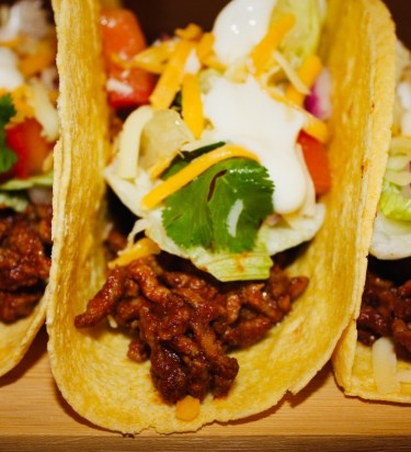 Close up of a beef taco with all the toppings.
