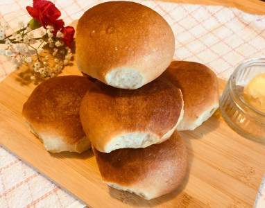 Super soft milk bread rolls stacked on top of each other and served on a wooden chopping board.