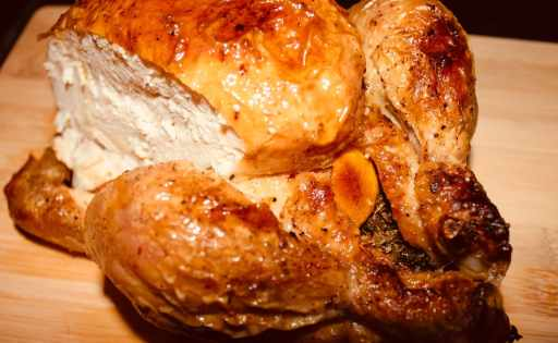 A full roasted chicken with crispy skin and succulent chicken pieces served on a wooden board