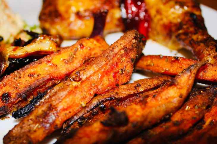 Crispy Sweet potato wedges on a white plate with peri peri chicken