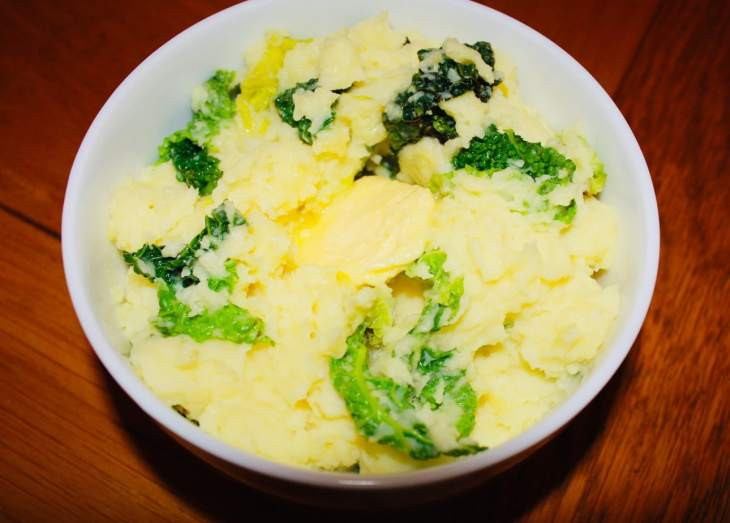 Traditional Irish creamy colcannon served in a side bowl with a knob of melting butter on top.