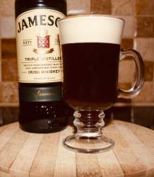 Freshly made Irish coffee place on wooden board. A bottle of Jameson whiskey behind it.