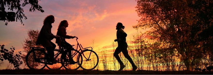 A man running at sunset, and two women cycling