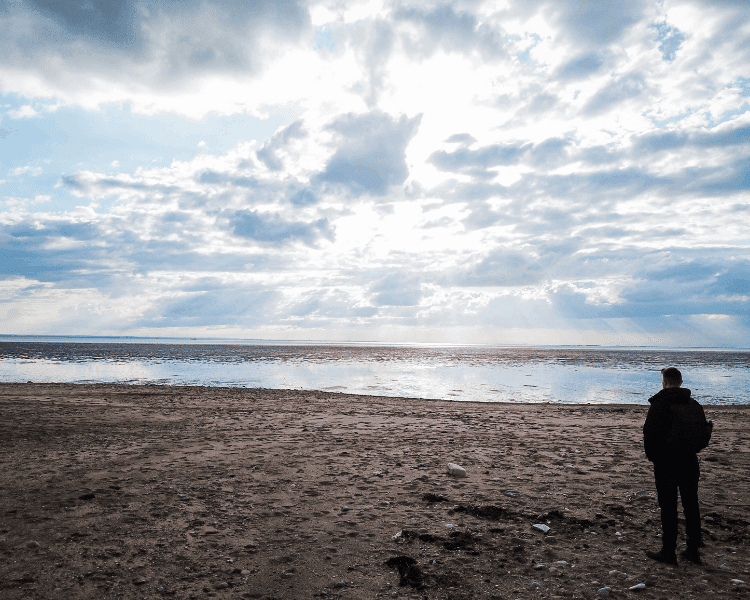 5 Benefits of Waiting on the Lord - Man on a beach looking out to sea.