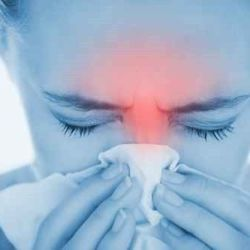Woman blowing her nose with highlighted red sinus pain