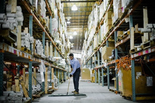 Warehouse Worker Sweeping --- Image by © Sean Justice/Corbis