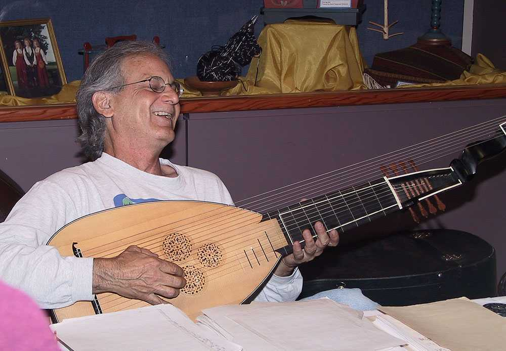 Terry Schumacher smiling while playing the lute