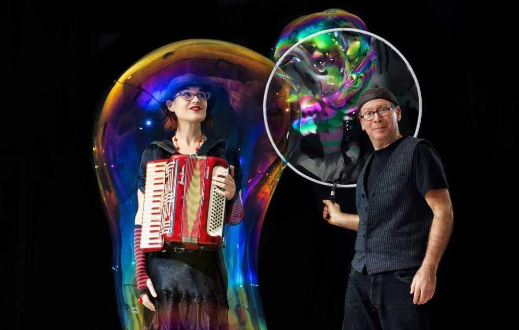 The Amazing Bubble Man engulfs a woman inside of a soap bubble